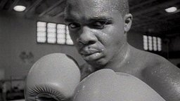 still, black & white image of an African American male boxer wearing boxing gloves from the documentary film 'Fight to the Max'