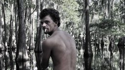 still, color image of shirtless Caucasian male with back facing camera and looking over his sholder with bayou in background take from documentary film 'The Other Side'